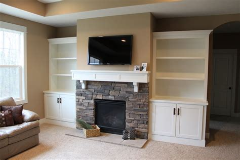 cabinets next to fireplace built in shelves surrounding fireplace built in