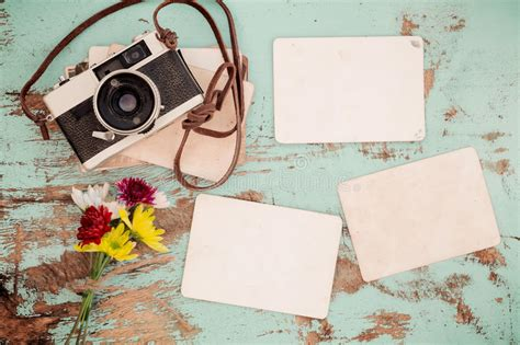 retro camera  empty  instant paper photo album  wood table  flowers border design