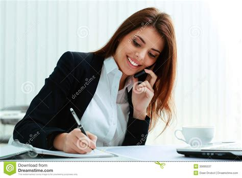 while on the phone businesswoman talking on the phone and writing notes