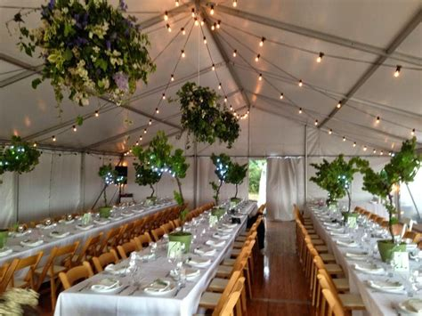 marquee structure festoon lighting wooden padded folding chairs banquet tables integrated