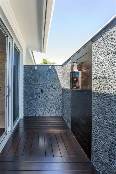 outdoor shower  pebble stone walls hgtv