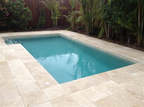 spellbinding travertine pool waterline tile with bamboo
