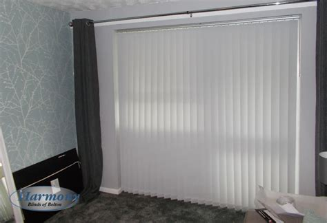 wide vertical blind in white fabric covering patio doors