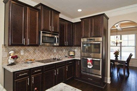 dark cabinets contrast beautifully  chrome hardware  stainless steel appliances