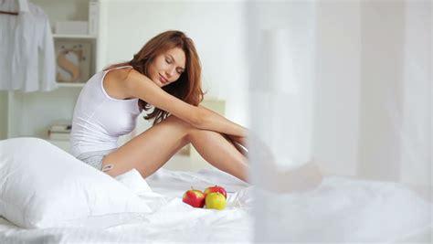teen girl stroking  sitting  white bed