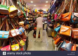 People shopping for handbags in a leather goods store shop ...