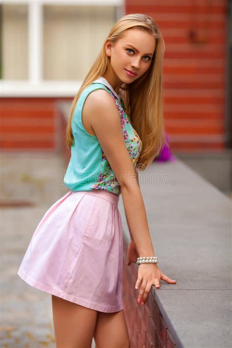 Beautiful Blonde Woman With Pink Skirt Posing Outdoor