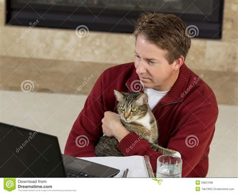 mature man holding  family pet  working  home