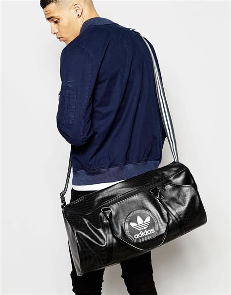 lyst adidas originals perforated duffle bag  black  men
