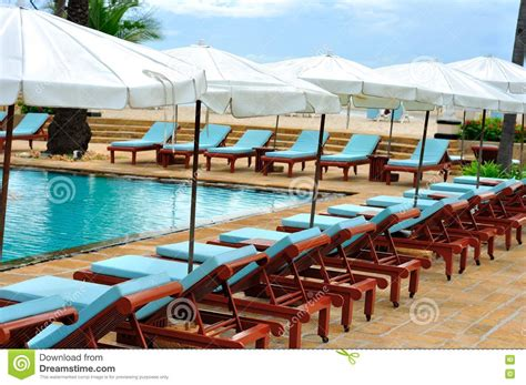wooden lounge chairs  row  swimming pool stock