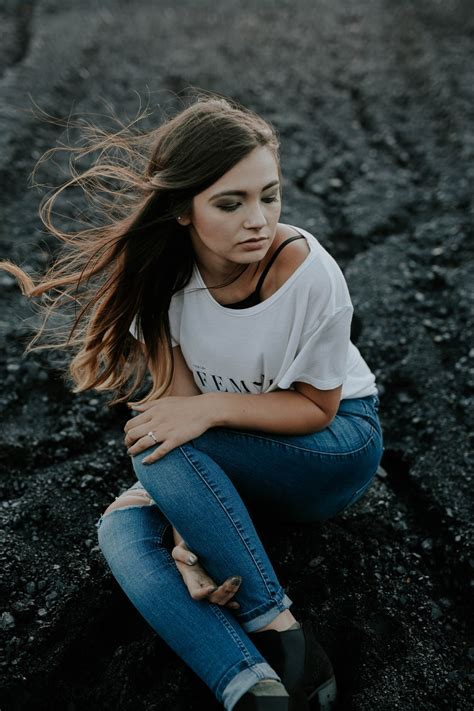 woman wearing scoop neck shirt  distressed jeans sitting  ground  holding knee photo