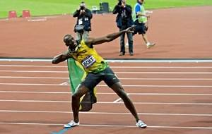 Usain Bolt defends 100m title with new Olympic record ...