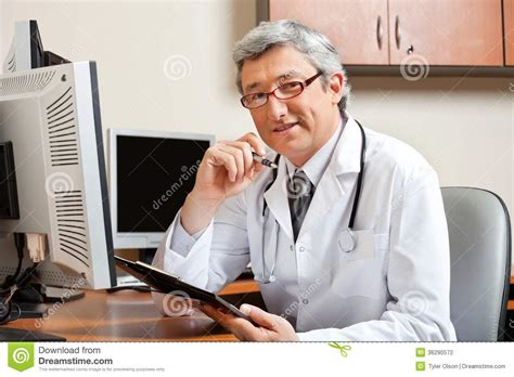doctor s office front desk jobs doctor sitting at desk in front of computer stock
