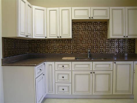 Copper tin backsplash and distressed white cabinets   The