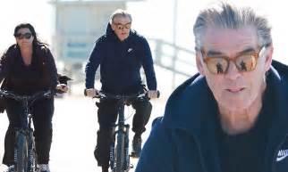 Pierce Brosnan enjoys a beachside bike ride with wife ...