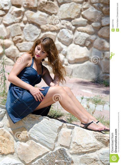 cute fashion woman sitting   edge   wall stock