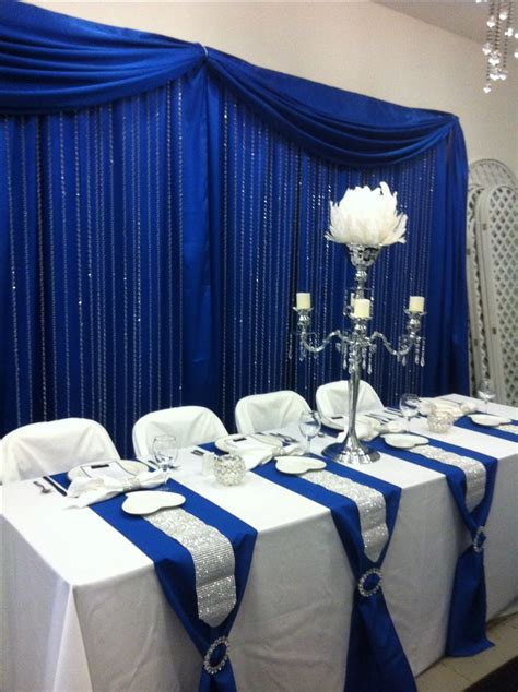 Head table with royal blue back drop and crystal step