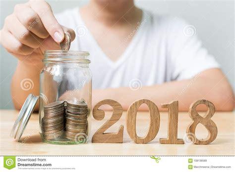 man putting coin  jar  wood number  year save
