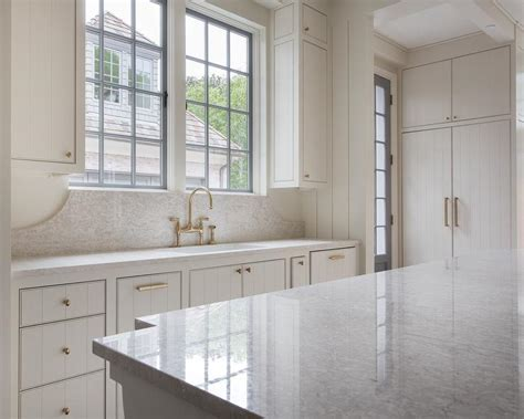 White Shiplap Kitchen Cabinets With Aged Brass Oval Knobs