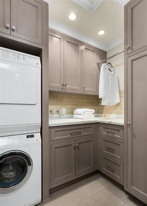 gray laundry room cabinets with tension pole clothes hanger dryer transitional laundry room