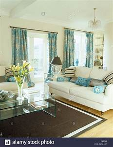 patterned turquoise curtains and cream sofas in cream With cream and black living room furniture