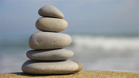 stacked rocks zen a stacked pile of rocks on a calm ocean beach suggests zen peace and pleasant travel stock