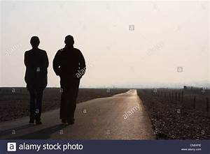 two people walking into the distance along a straight path ...