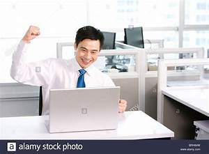 Happy office worker at his desk Stock Photo, Royalty Free ...