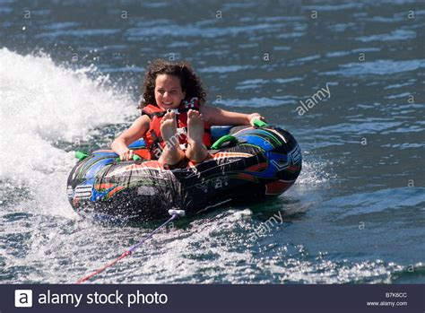 Inner Tube Behind A Boat by Young Woman On Inner Tube Behind Boat Okanagan Centre Bc