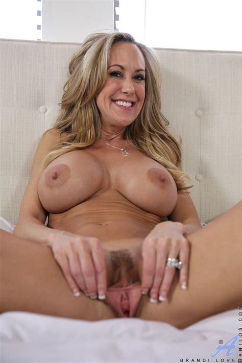 delicious blonde milf brandi love jumps out of her dress to spread her hairy pussy in bed