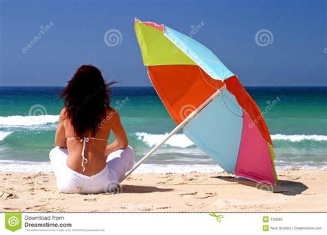 femme s asseyant sous le parasol color 233 sur la plage sablonneuse blanche photo libre de droits