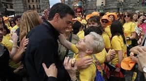 pedro sanchez reparte besos  posados en una marcha de