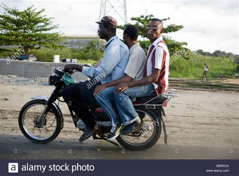 Three Men Share A Motorbike Along The Road Leading Out Of