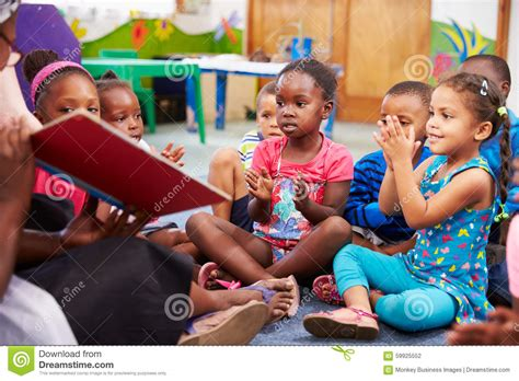 reading a book with a class of preschool children 294 | teacher reading book class preschool children 59925552