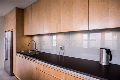 armadietti lavoro frigorifero nero in cucina luminosa immagine stock