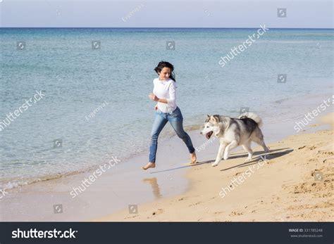 young woman running  husky dog stock photo