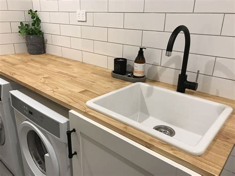 wooden bench top subway tiles and matte black tapware in