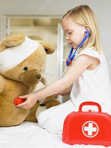 Girl playing doctor with teddy bear - Stock Image F003 ...
