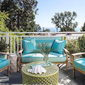 teak outdoor sofa  blue cushions  green  blue