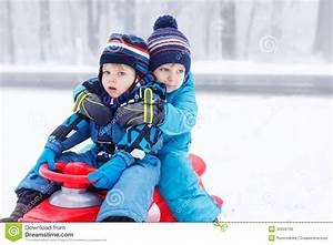Two Little Kids Sitting Together On Sledge On Cold Day ...