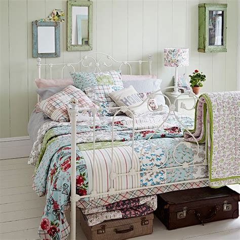 country bedroom with iron bed and patchwork quilt