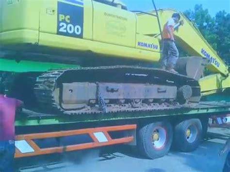 menaikan alat berat  atas truk operator eskavator