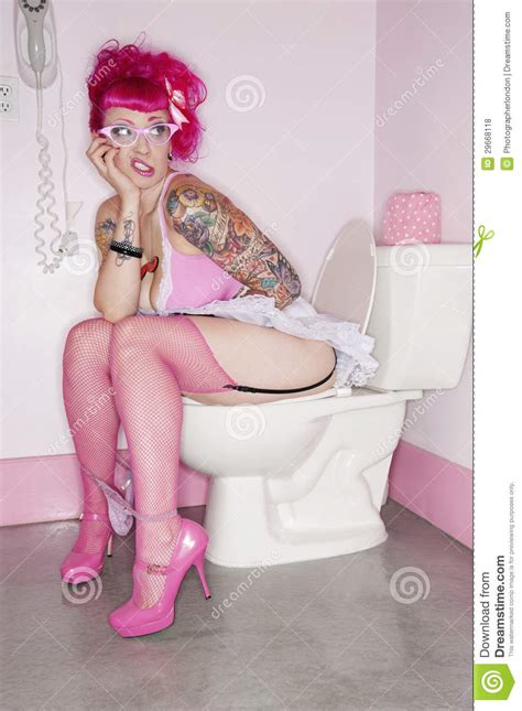 tattooed sitting on toilet seat with