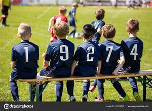 Kids sport team sitting on a bench. Group of kids soccer ...