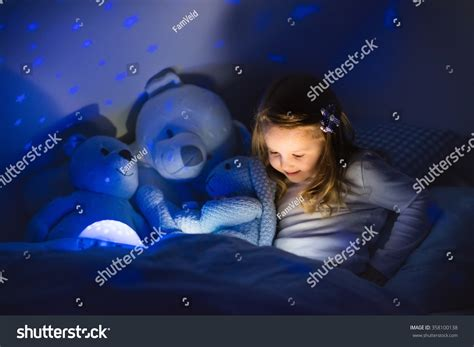 Little Girl Reading A Book In Bed Dark Bedroom With Night