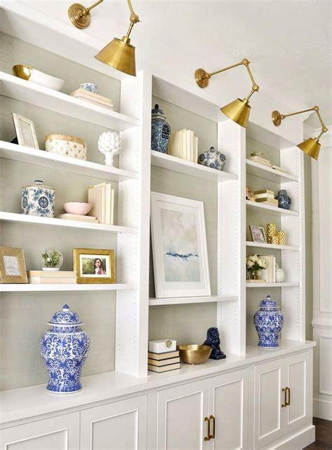 brass sconce lights over built in shelves shelf styling