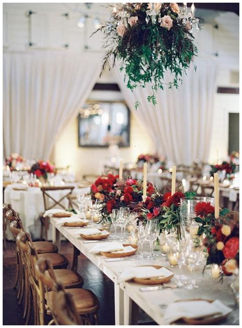 fall wedding reception table  brilliant red florals