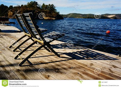 grey wooden  chairs  fjord norway stock image