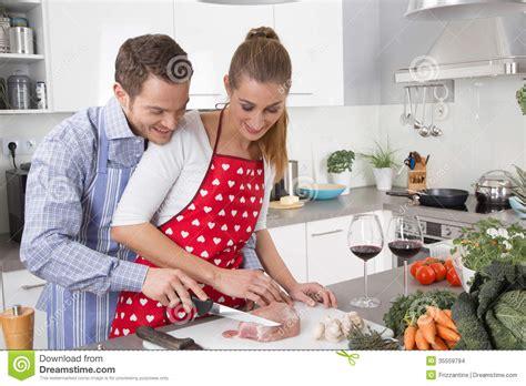 les couples dans l amour faisant cuire ensemble dans la cuisine et ont l amusement images stock