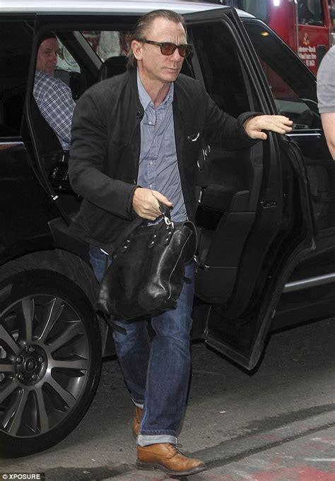 Daniel Craig reveals a very high hairline as he tries a
